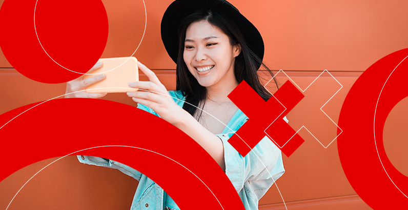 Garota asiática usando chapéu olhando celular