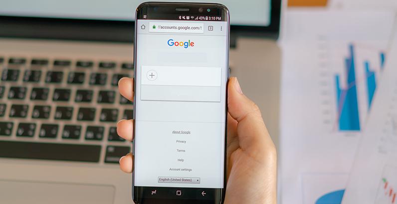 Pessoa segurando um smartphone cuja tela mostra o Google